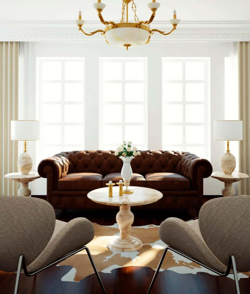 Classy living room features brown chesterfield sofa and gray stylish chairs with a round marble table in the middle. It is lighted by a gold chandelier and table lamps that sit on end tables.