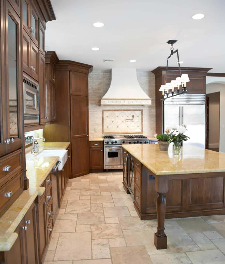 Spacious kitchen boasts a central island topped with beige marble counter and surrounded with matching cabinetry and stainless steel appliances.