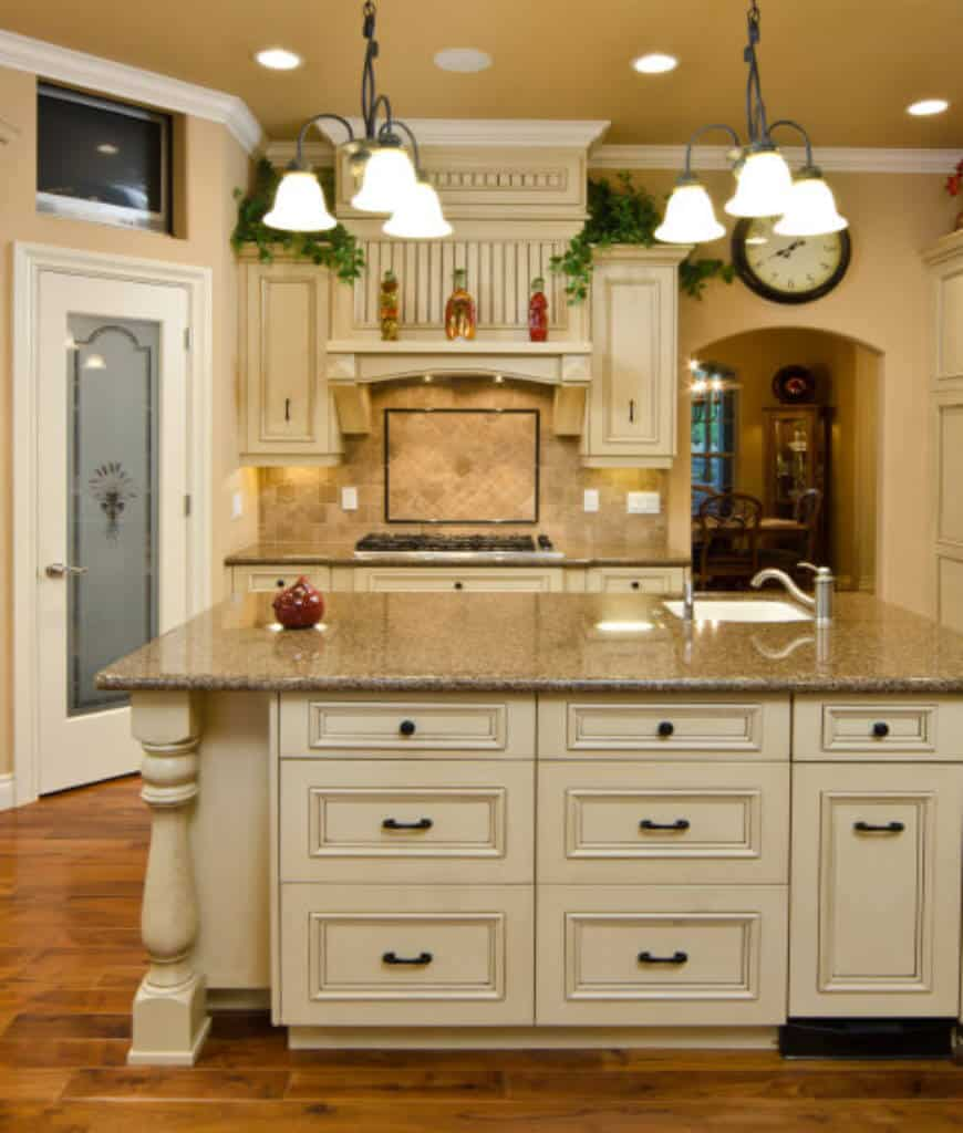Fresh kitchen showcases dome chandeliers and a white breakfast island that matches with the cabinetry and vent hood accented with indoor plants.