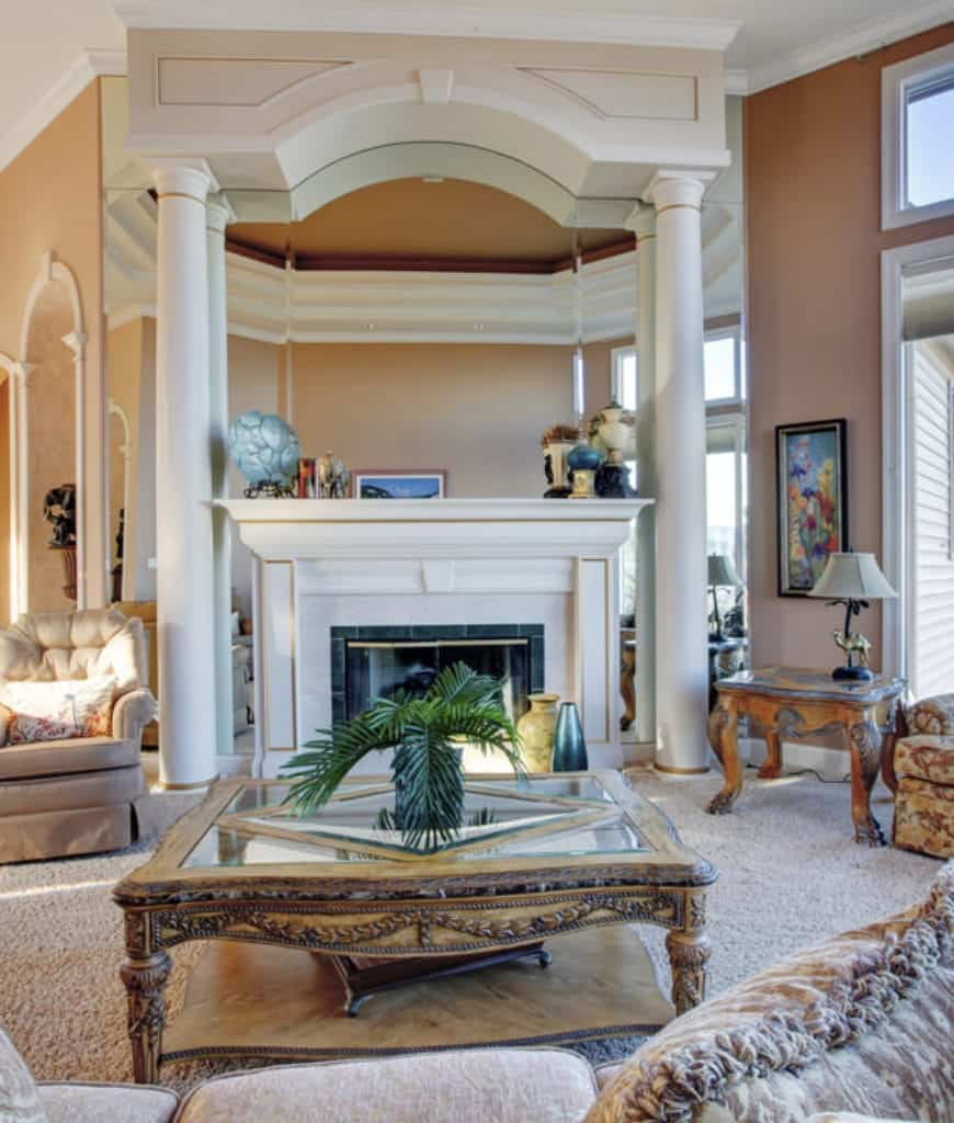 Deluxe living room boasts a glass top coffee table and beige tufted armchair that sits next to the luxury fireplace framed with columns.