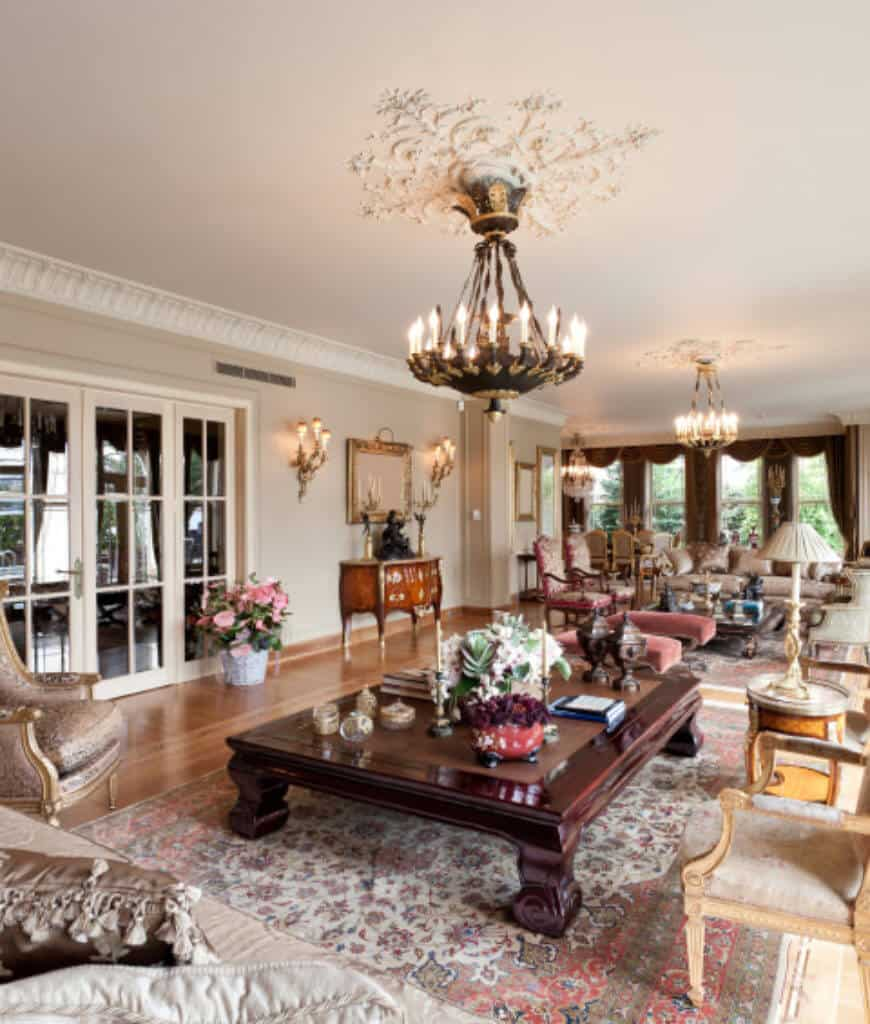 Large living room offers multiple seating areas lighted by wall sconces and candle chandeliers that hung from the white ornate ceiling.