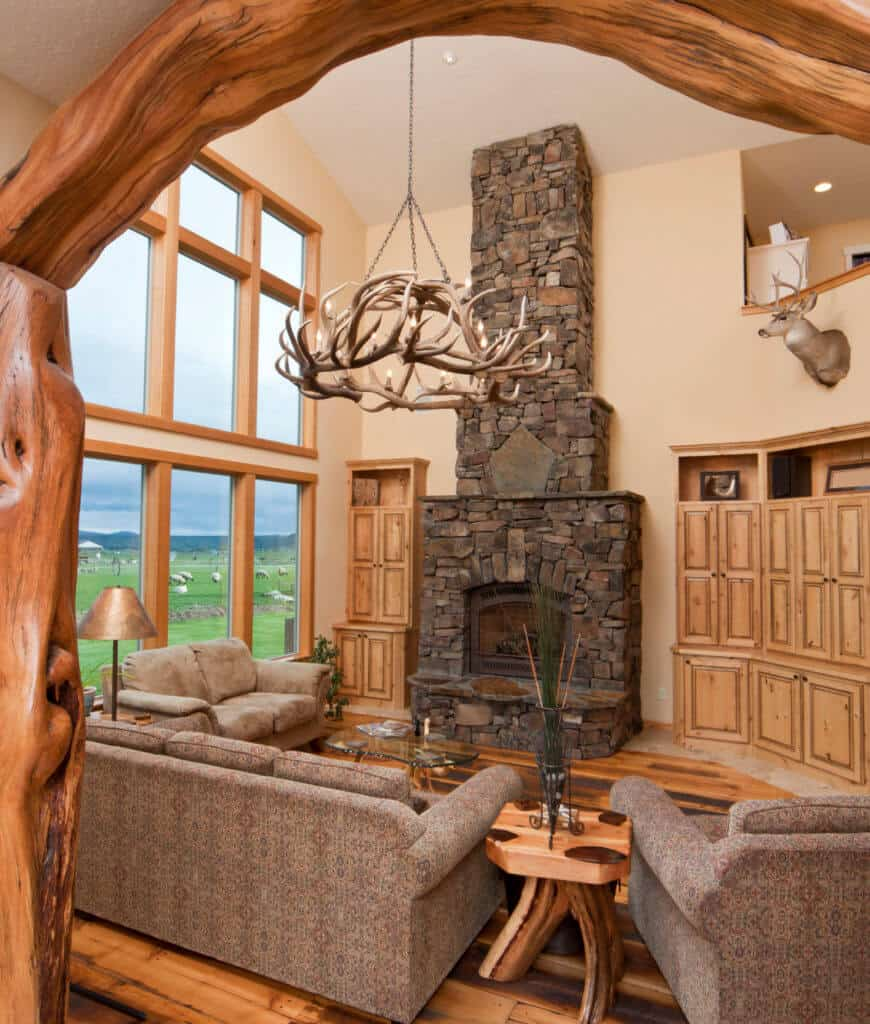 An arched doorway opens to this living room with hardwood flooring and glass paneled windows overlooking the expansive lush lawn. It includes antler chandelier and stone fireplace fixed in between built-in cabinets.