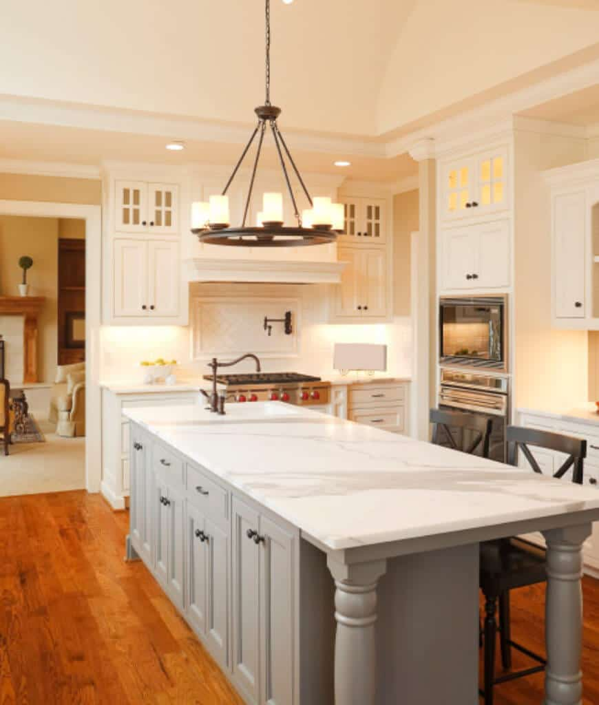 A round chandelier hangs over the gray island bar topped with marble counter in this kitchen with white cabinetry and rich hardwood flooring.