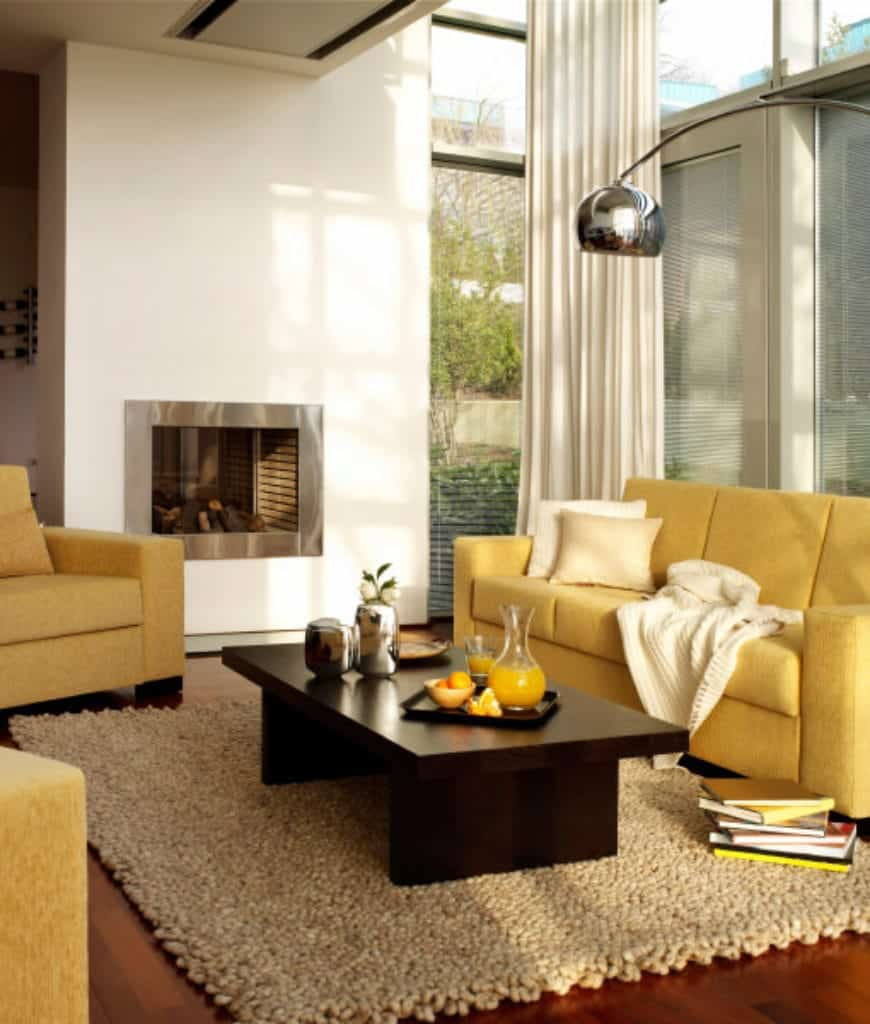 Contemporary living room accented with yellow sectional and armchairs surrounding a dark wood coffee table lighted by a chrome arched floor lamp.