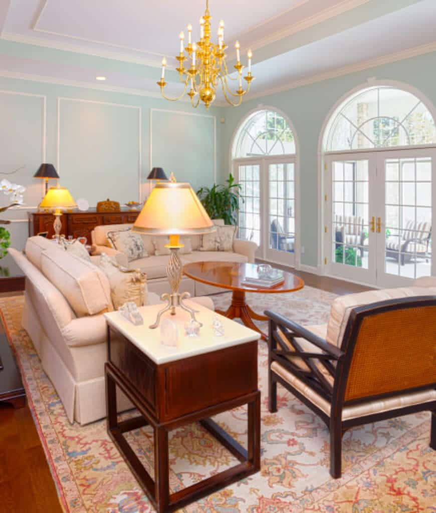Airy living room with French windows and door that leads to the patio filled with striped armchairs. It includes beige skirted sofas and cushioned chair along with a round coffee table lighted by a gold chandelier.