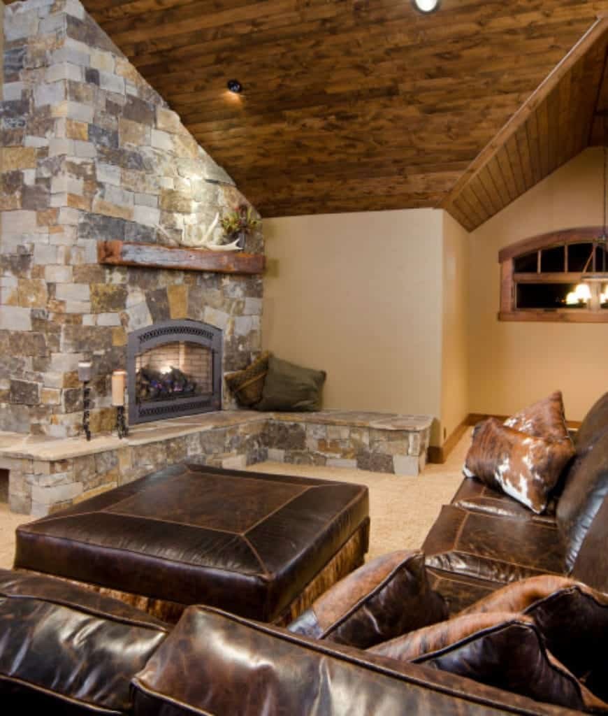 Craftsman living room with brown leather sectional and ottoman across the stone brick fireplace lined with a rustic wood mantel.