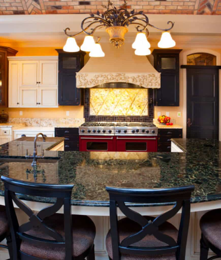 A closeup look at this kitchen accented with red dual oven range that sits beneath an ornate vent hood accompanied by white and black cabinetry.