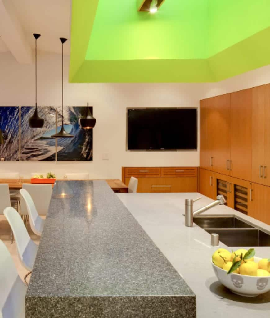 Modern eat-in kitchen accented with a neon green ceiling and lovely multi-panel wall art mounted on the white wall. It has wooden cabinetry and a gray kitchen island attached with a raised eating counter that's lined with white bar chairs.