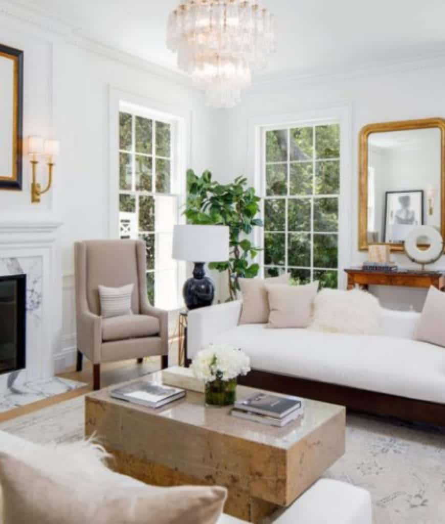 Fabulous living room with a glossy coffee table and sleek white sofas filled with furry and beige pillows that complement with the armchair. It is lighted by a cascading chandelier and brass sconces mounted above the marble fireplace.