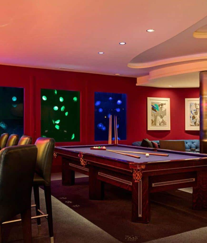 Deluxe game room decorated with white framed wall arts and custom jellyfish tanks that add class and a sense of tranquility at the same time. There's a pool table nestled in between black leather chairs and blue chesterfield sofa.