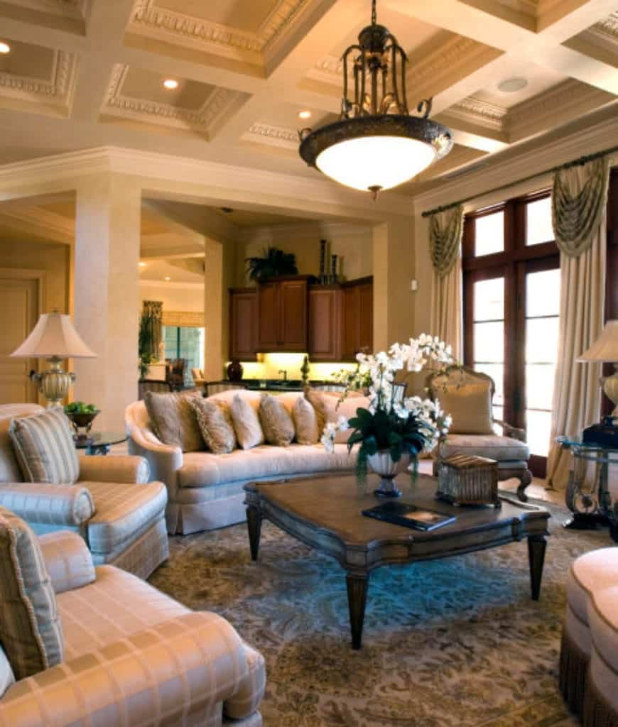 A huge pendant light that hung from the ornate coffered ceiling illuminates this living room boasting a wooden coffee table surrounded with beige armchairs and skirted sofa filled with fluffy pillows.