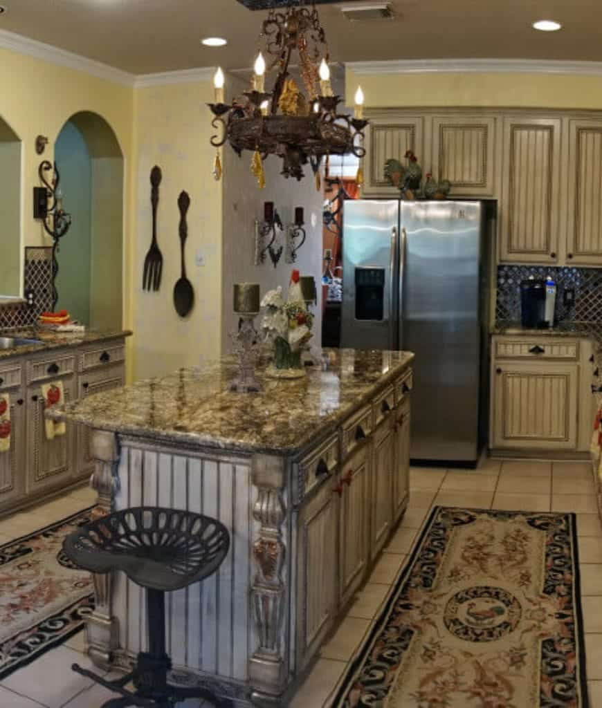 Yellow kitchen designed with large spoon and fork wall decor along with floral kitchen runners that lay on the white tiled flooring.