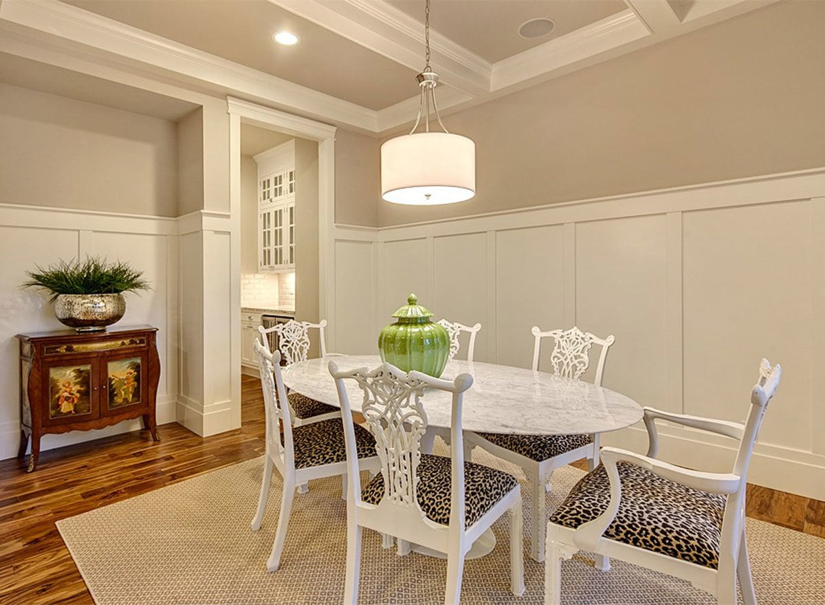 This dining room features an oval marble table paired with elegant cushioned chairs. It has a beamed ceiling and light gray walls adorned with white wainscoting.