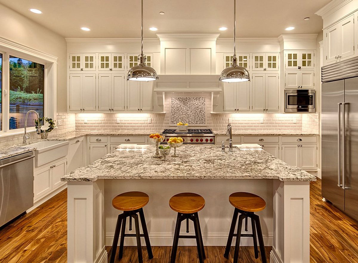 This white kitchen equipped with stainless steel appliances and a farmhouse sink is softened by ambient lighting from the chrome dome pendants and recessed ceiling lights.