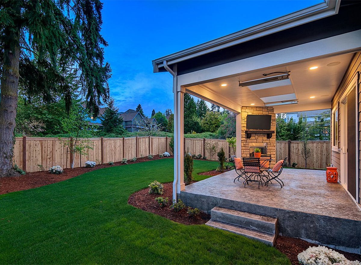 The lush green lawn bordered by plants and wooden fence radiates a serene atmosphere to this backyard.