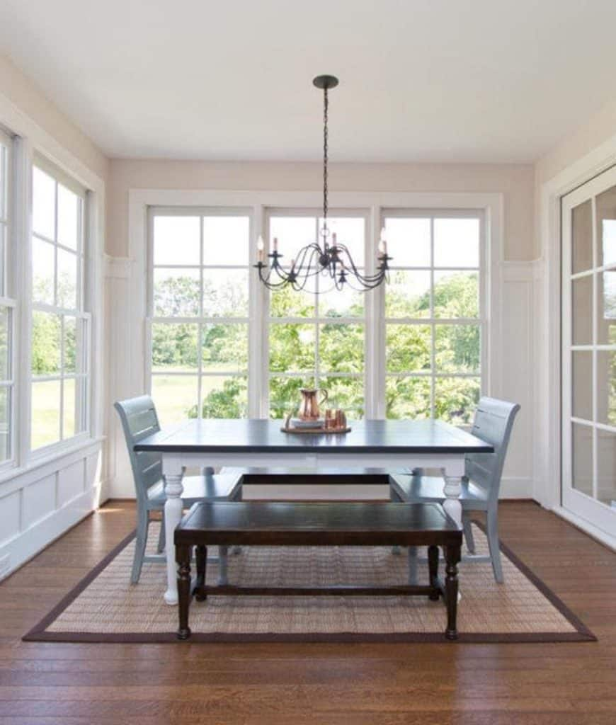 An airy dining room with white framed windows and wicker rug that lays on the wood plank flooring. It includes a gray dining set with wooden benches illuminated by a wrought iron chandelier.