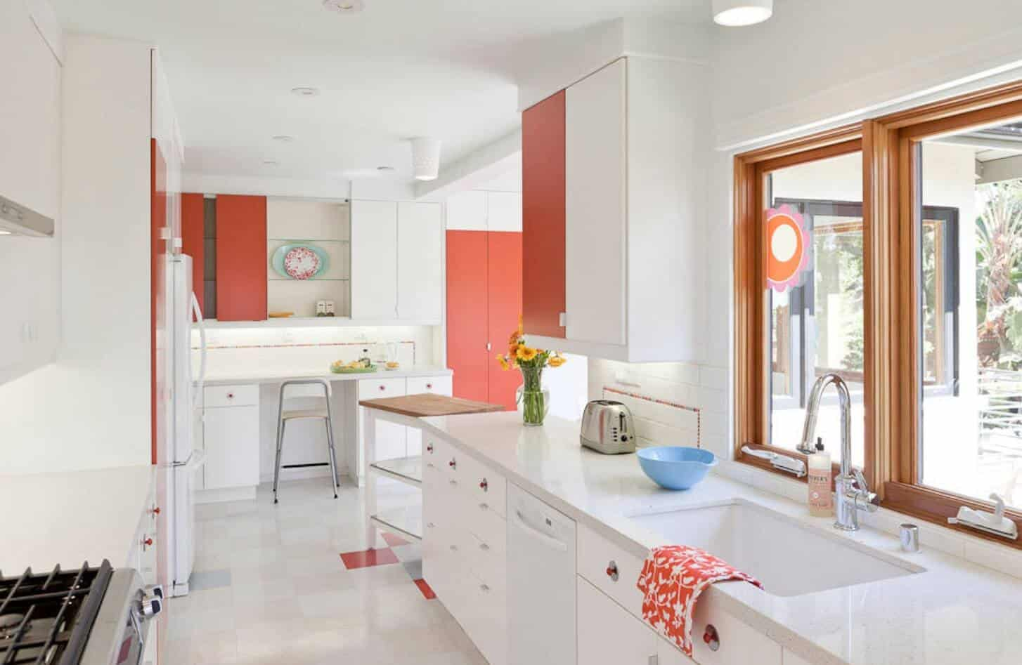 Ranch kitchen with checkered flooring and wooden framed windows showcases white appliances and cabinetry with subtle red accents.
