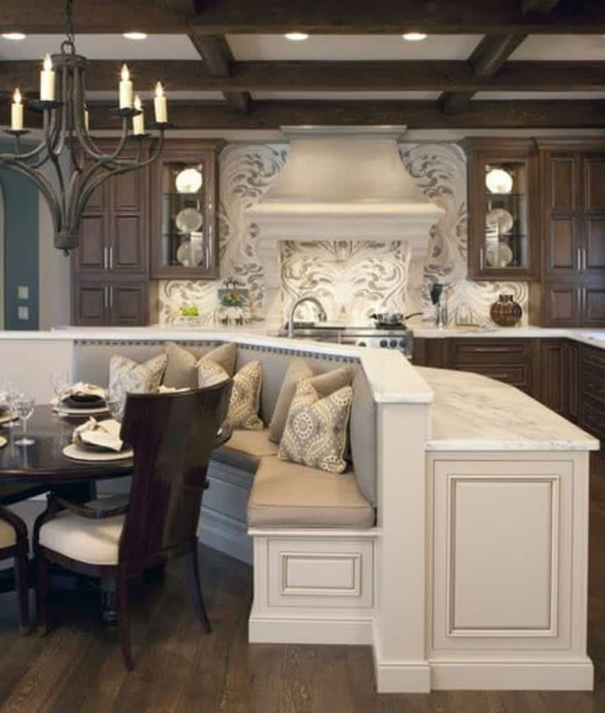 Sophisticated kitchen with white range hood fixed on the decorative backsplash complements with the island bar attached with breakfast nook. It is accompanied by a wooden dining set lighted by a vintage chandelier.