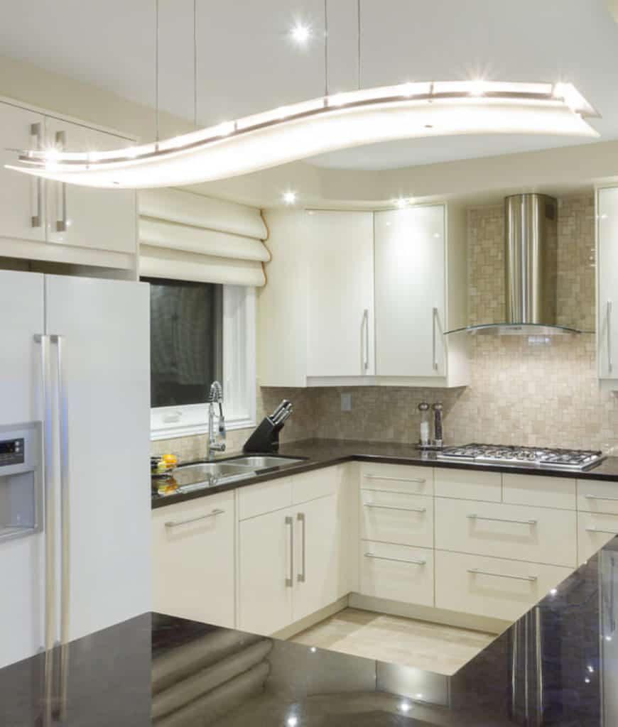 A stylish pendant light illuminates this kitchen boasting white appliances and cabinetry along with a stainless steel range hood fixed to the mosaic backsplash tiles.