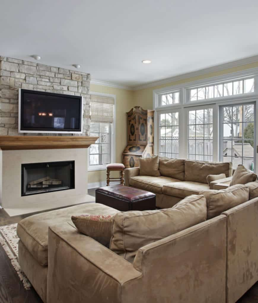 Fresh living room with brown velvet sectionals and a fireplace fixed to the stone brick pillar lined with a wooden mantel.