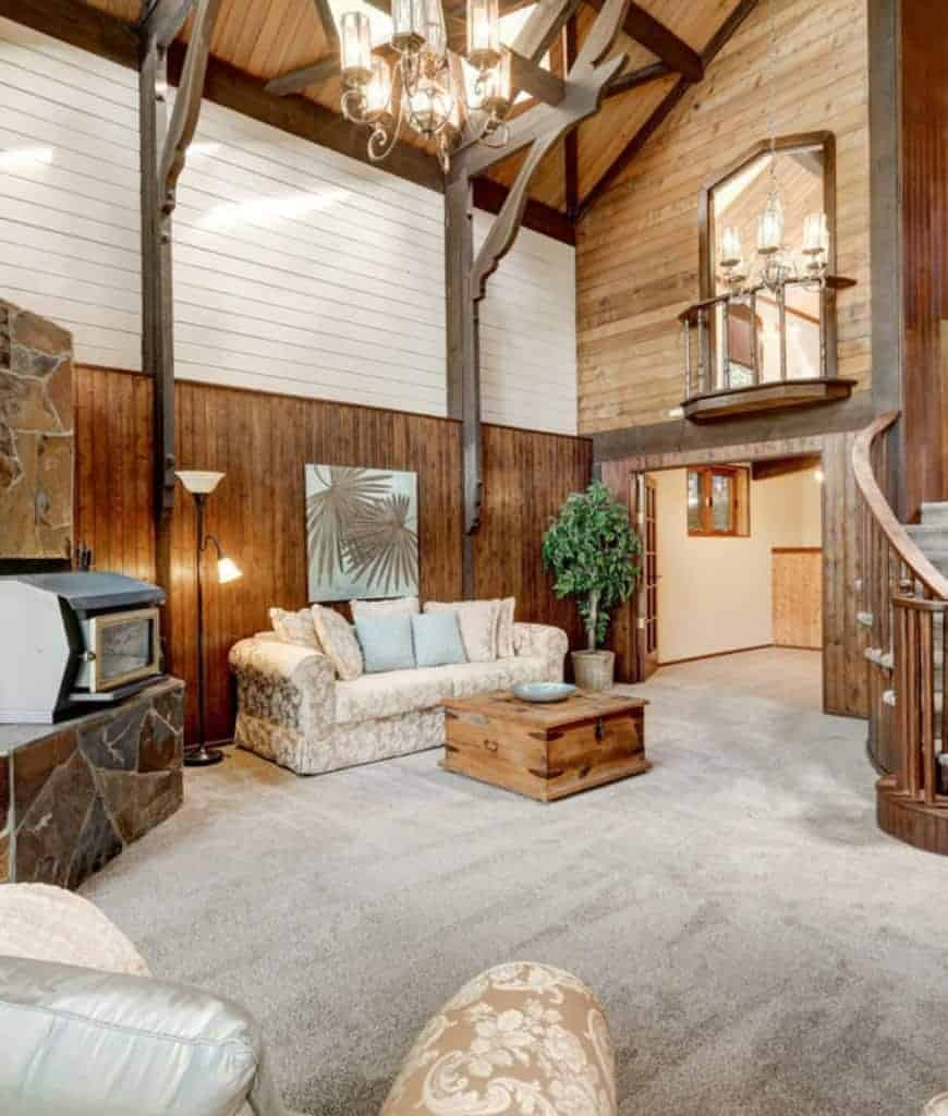 Rustic living room boasts carpet flooring and wood plank ceiling with a hanging chandelier. It has floral seats accompanied by chest coffee table and fireplace.