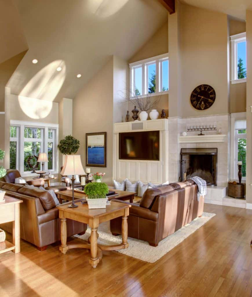 Beige living room with cathedral ceiling and hardwood flooring topped by a shaggy rug. It includes wooden coffee and side tables along with brown leather sofas facing the television fitted to the white wainscoted wall.