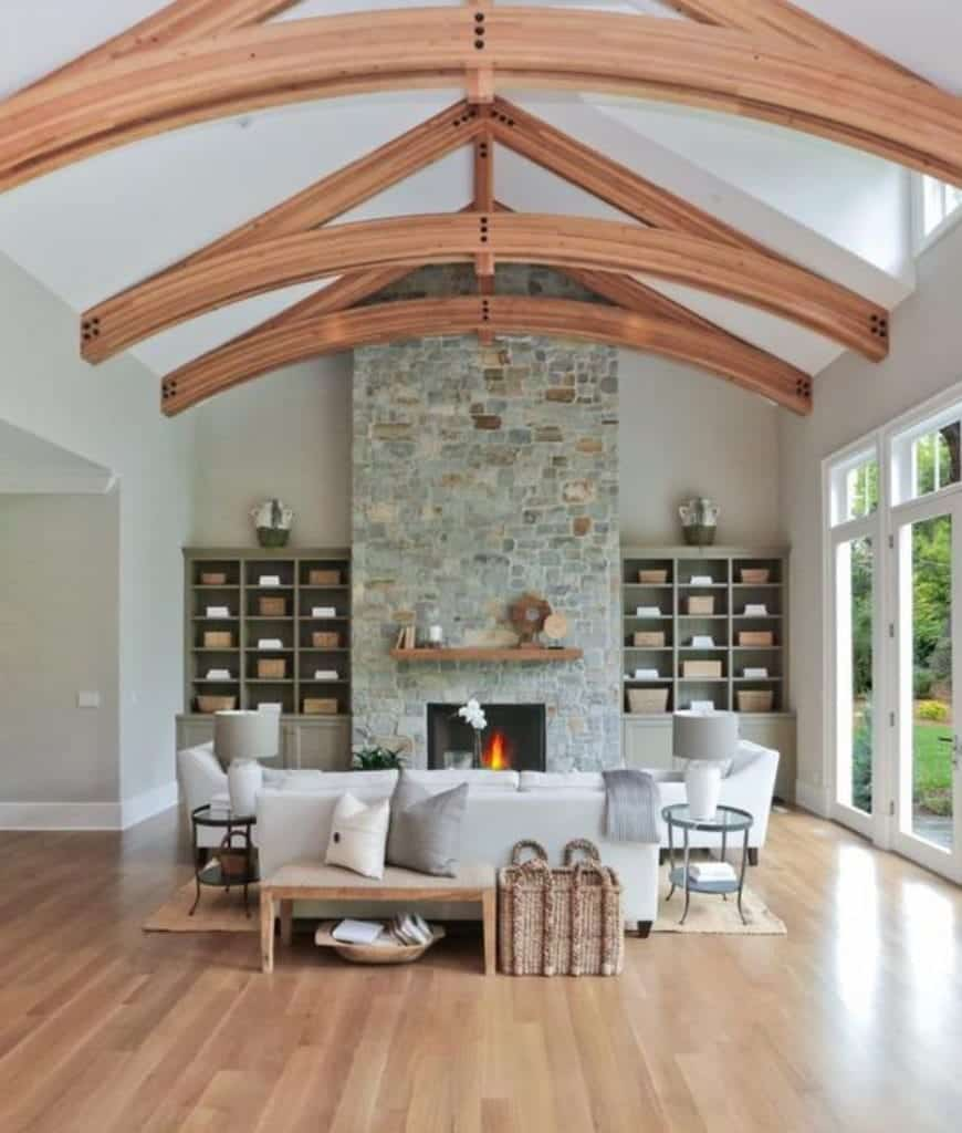 Rustic living room with a wood plank flooring and high cathedral ceiling framed with natural wood beams. There's a fireplace fixed to the stone pillar in between built-in shelvings.