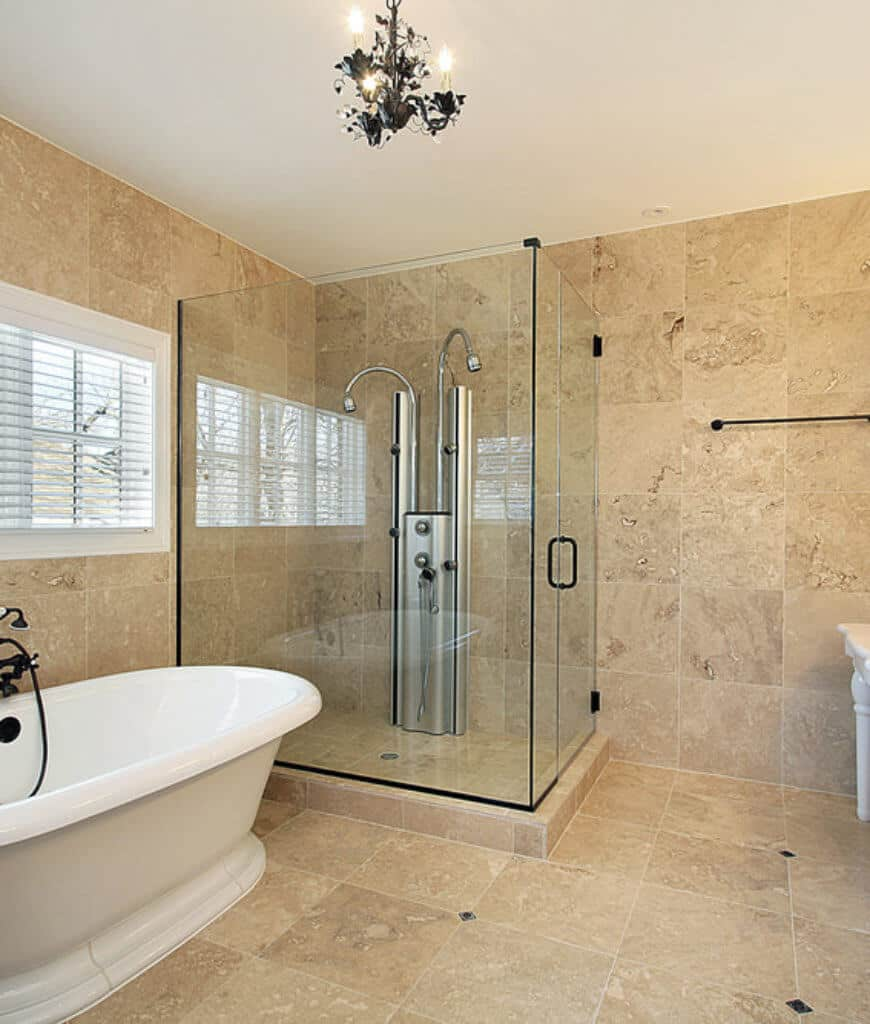Primary bathroom features a black chandelier and freestanding bathtub that sits next to the walk-in shower fixed on the marble tiled wall.