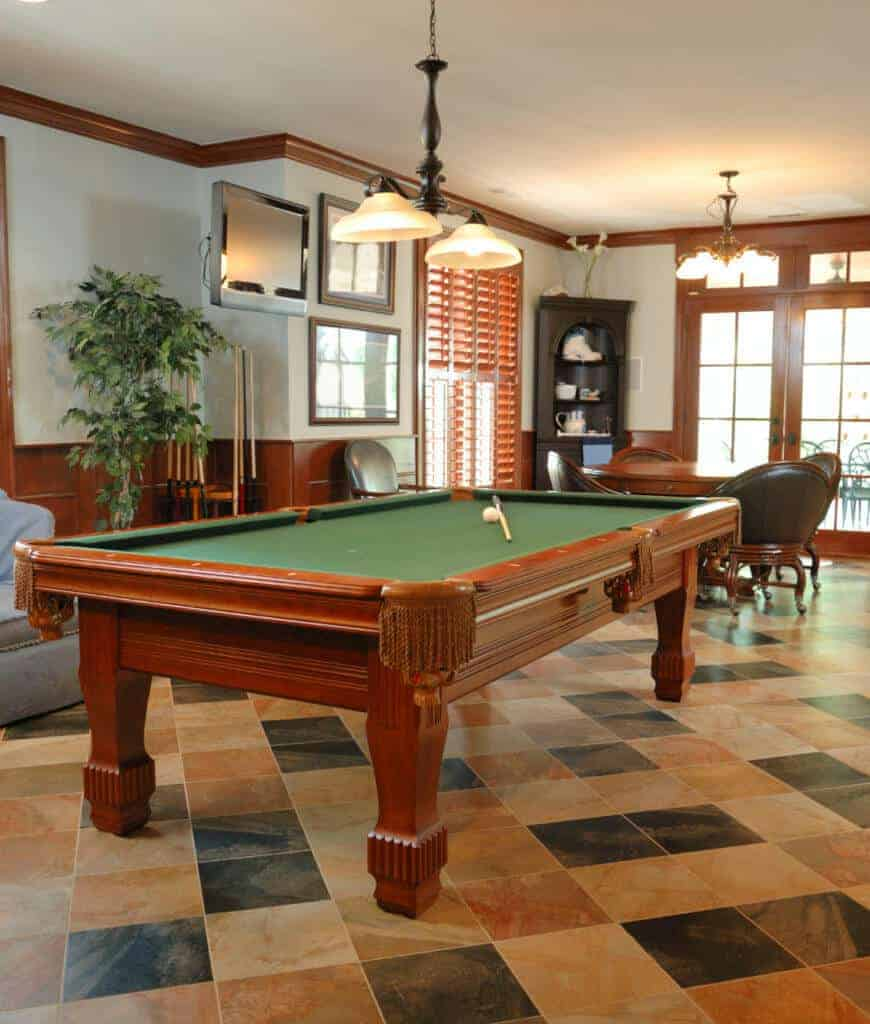 A wrought iron pendant hangs over the pool table situated across the seating area by the French door. There's a potted plant in the corner which gives a refreshing ambiance to the room.