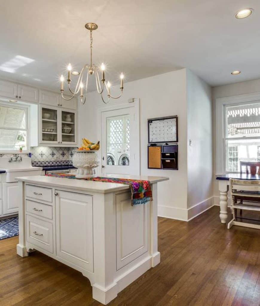 White kitchen boasts a candle chandelier that hung over the central island lined with a colorful runner. It has glass front cabinets and dining set by the picture windows illuminated by recessed lights.