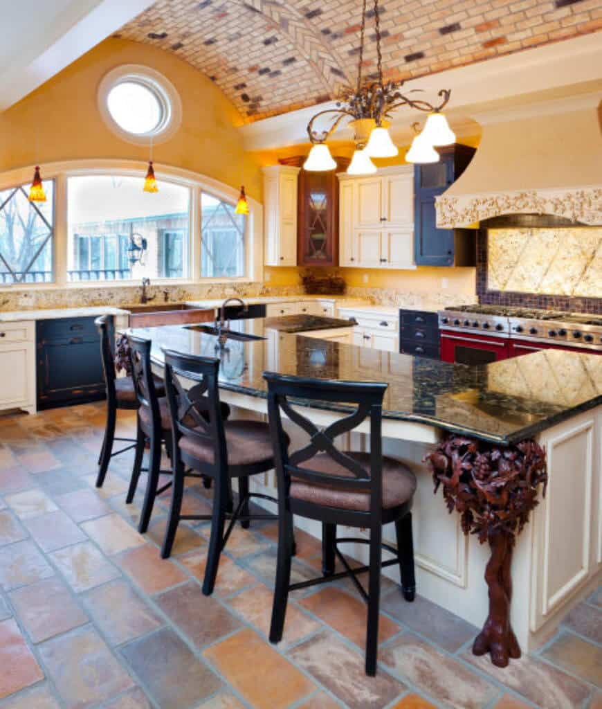 Yellow kitchen with a U-shaped breakfast bar paired with black counter chairs and a classy chandelier that hung from the barrel-vaulted ceiling clad in decorative bricks.