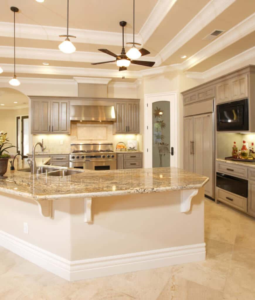 Bright kitchen with a curved island bar fitted with dual sink and illuminated by pendant lights that hung from the tray ceiling framed with white crown moldings.