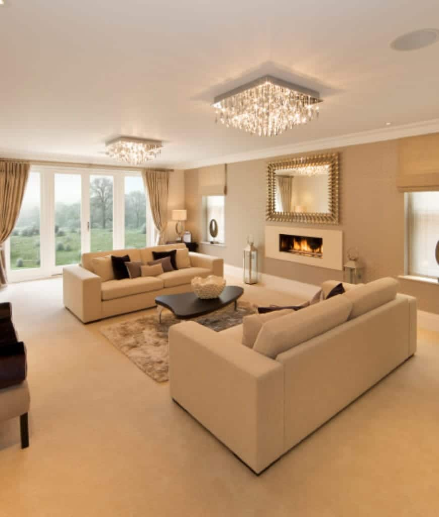 Classy living room showcases a pair of fancy flush mount ceiling lights that hung over the beige couches and a stylish mirror mounted above the sleek fireplace.