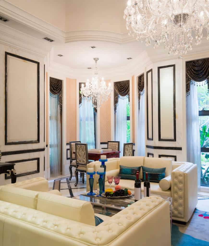 Elegant white living room showcases glamorous chandeliers and leather tufted loveseats accented with blue pillows that complement with the candle holders sitting on a mirrored coffee table.