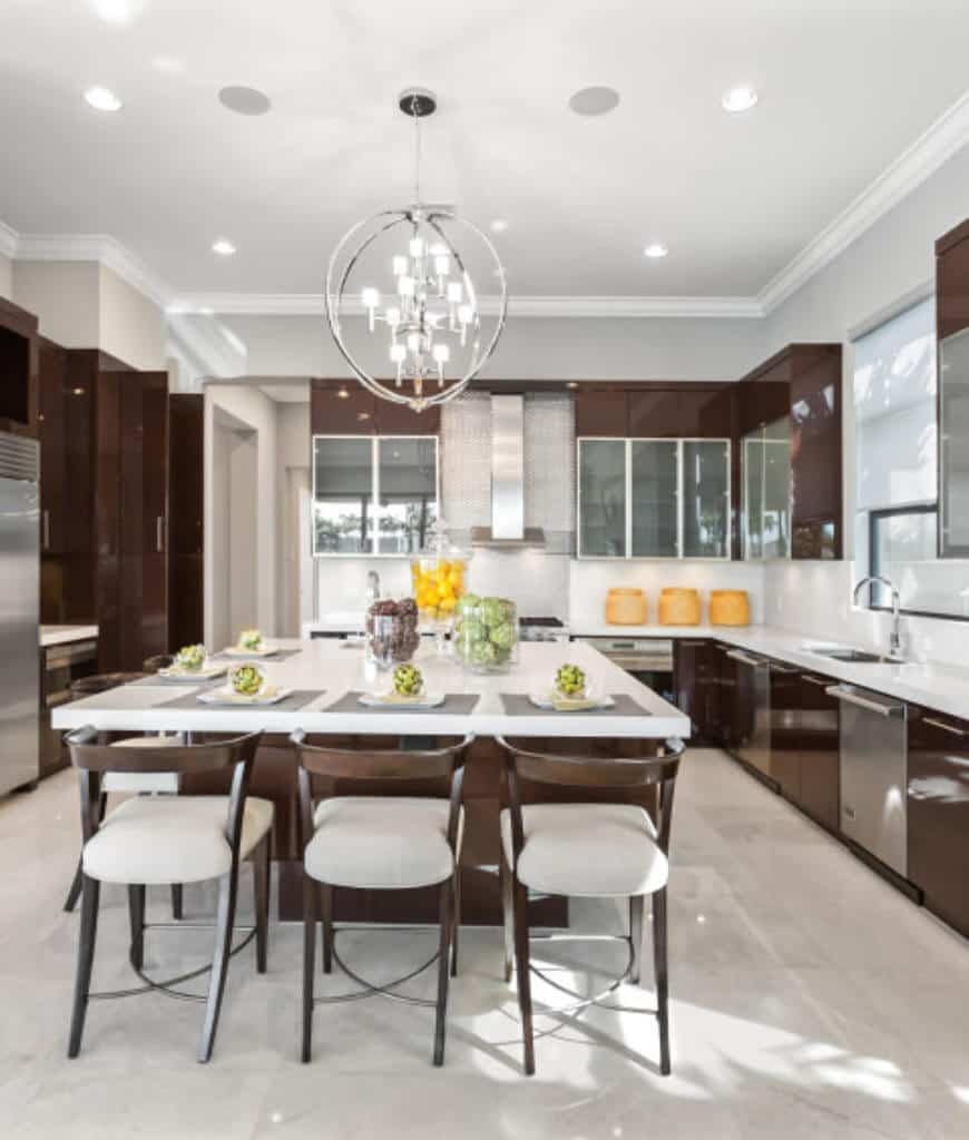 Modern kitchen boasts high gloss cabinetry that matches with the brown island bar topped with white quartz counter and lighted by a spherical chandelier.