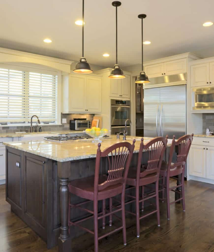 This kitchen offers louvered windows and stainless steel appliances inset fitted on the white cabinetry. It includes a wooden breakfast bar lined with black dome pendants and burgundy counter chairs.