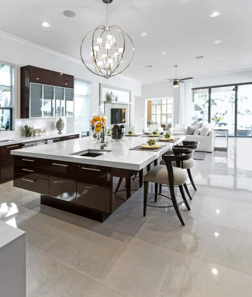 An open kitchen with an immense breakfast island lined with gray cushioned chairs and lighted by a spherical chandelier along with recessed ceiling lights.