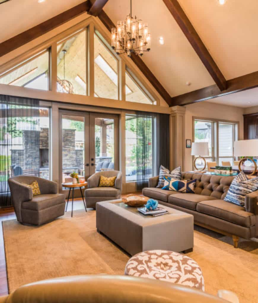Warm living room with gray tufted sectional and round back chairs along with a sleek ottoman lighted by a glass chandelier that hung from the cathedral ceiling lined with wood beams.