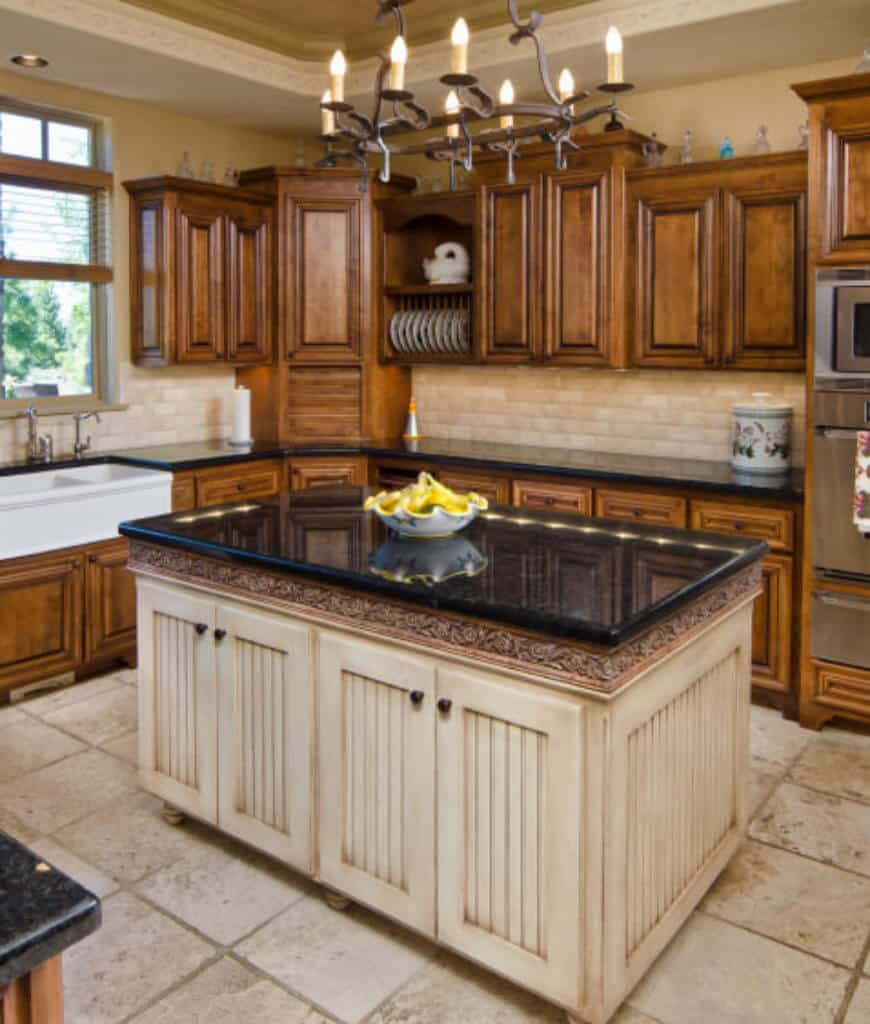 Rustic kitchen illuminated by a candle chandelier with hooks that doubles as a pot rack. It hangs over the white beadboard central island topped with black granite counter and yellow decorative bowl.
