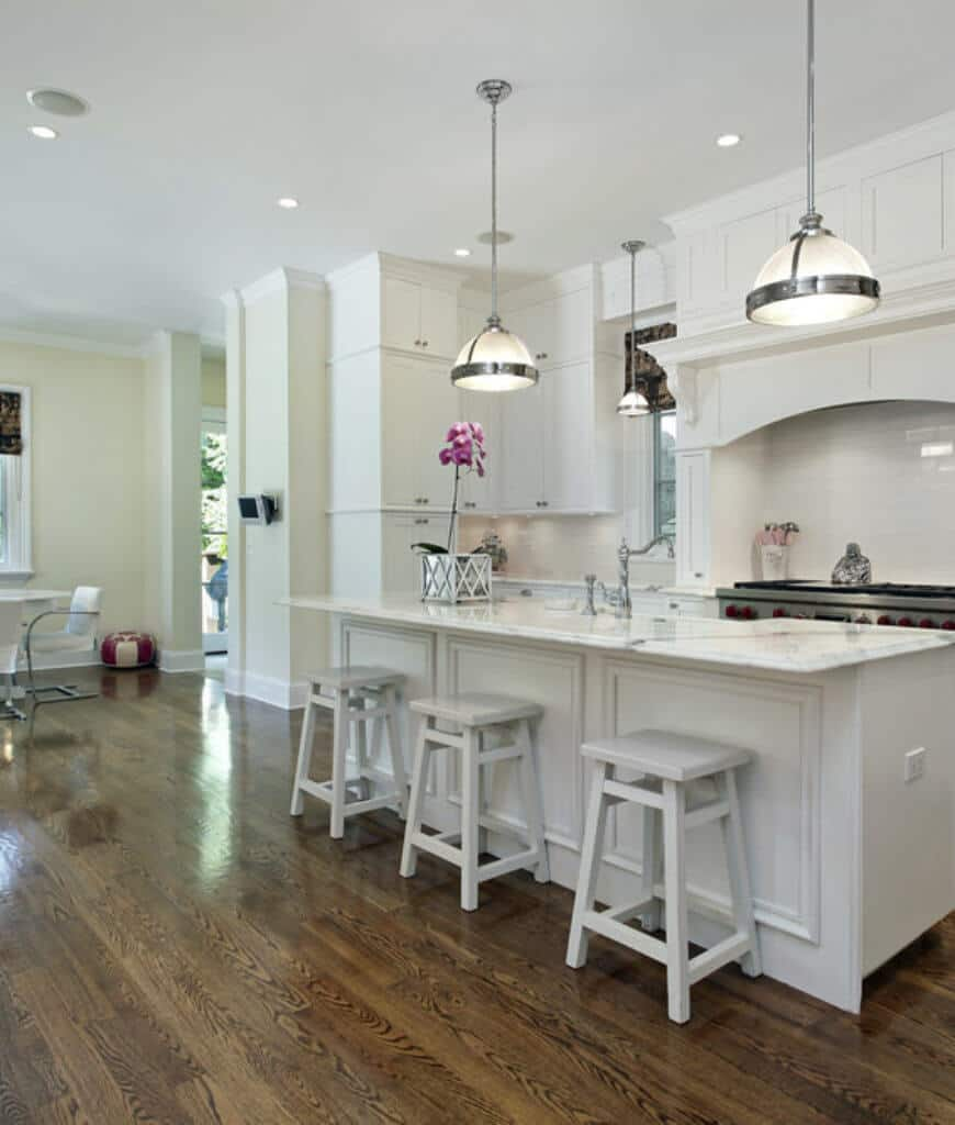 Small open kitchen with white cabinetry and range alcove that matches with the island bar lighted by dome pendants and recessed ceiling lights.