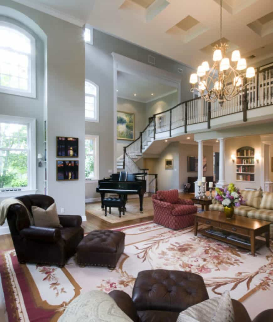 High ceiling living room features a baby grand piano and a wooden coffee table surrounded with mismatched seats over a shabby chic rug. It is illuminated by a vintage chandelier that hung from the coffered ceiling.