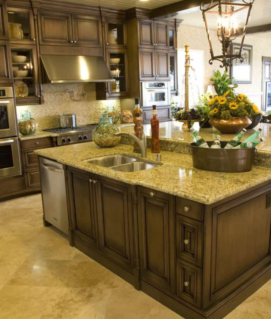 This kitchen showcases wooden cabinetry and an immense breakfast island fitted with dual sink and stainless steel oven. It has a raised eating counter lighted by a caged chandelier.
