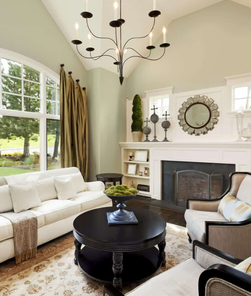 Fresh living room decorated with a sunburst mirror mounted above the fireplace that's fitted on the built-in cabinet with open shelving. It is lighted by a large candle chandelier that hung from the vaulted ceiling.