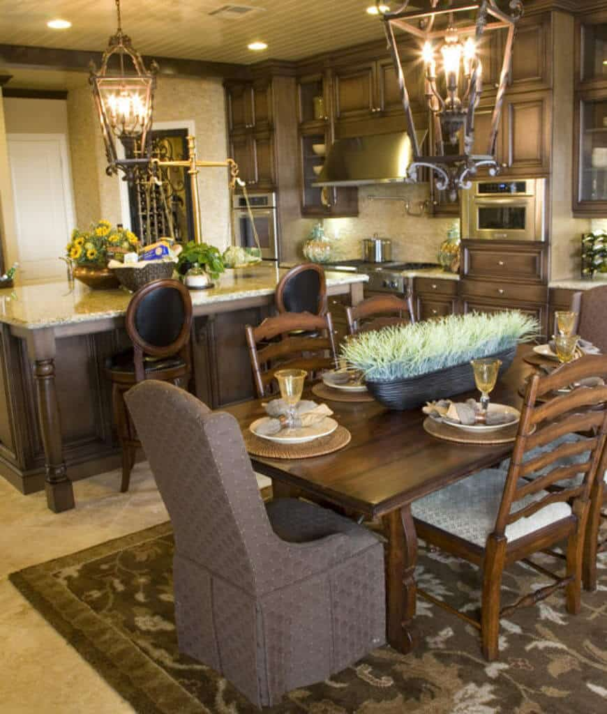 Eat-in kitchen illuminated by a pair of candle chandeliers that hung from the white shiplap ceiling. It has a breakfast island and wooden dining set that sits on a brown floral rug.