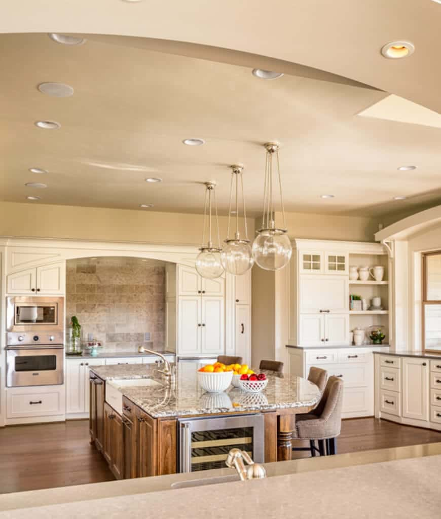 Glass globe pendants illuminate this kitchen boasting white cabinetry and a natural wood central island fitted with white vessel sink and wine fridge.