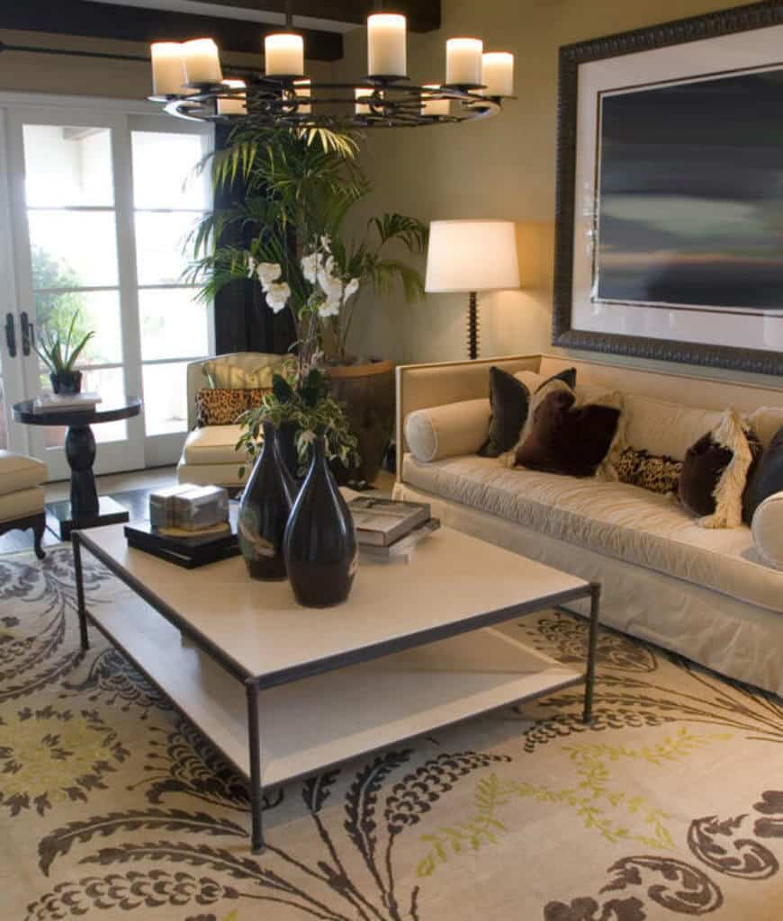 Tropical living room decorated with huge wall art that hung above the beige sofa filled with fluffy and furry pillows. It has leather chairs and a metal coffee table that sits on a printed rug lighted by a round chandelier.