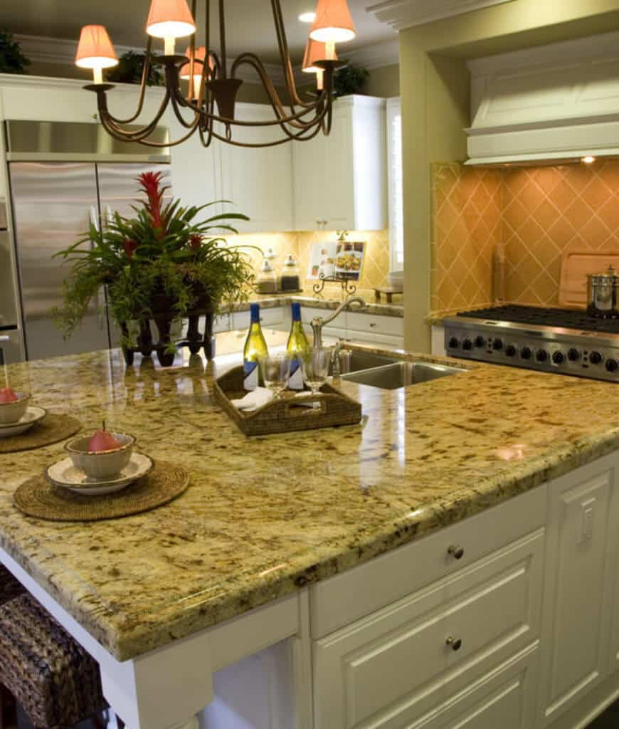 Tropical kitchen with diamond pattern backsplash and shade chandelier that hung over the white breakfast island topped with a marble counter and dual sink.