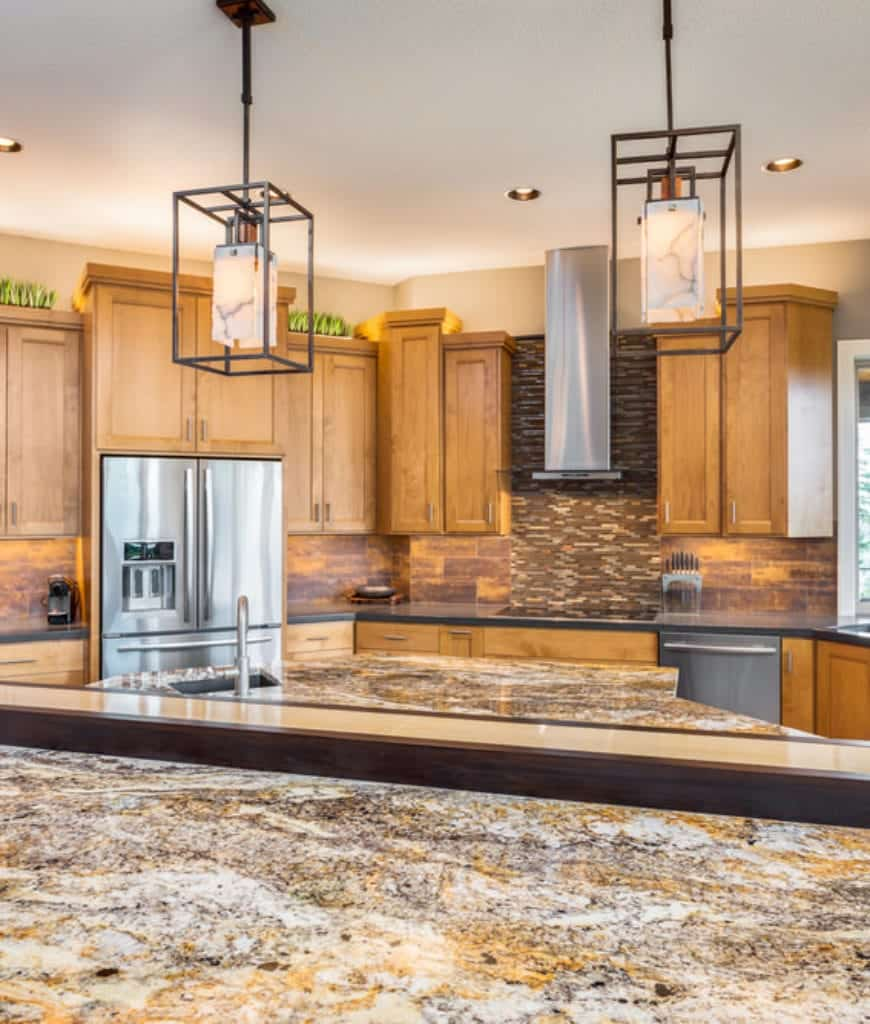 Marvelous kitchen features a sleek vent hood fixed on the linear mosaic tile backsplash along with a pair of caged pendants that hung over the marble countertop.