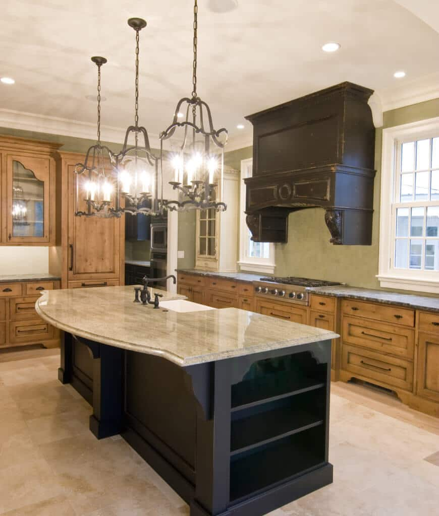 Candle chandeliers illuminate this kitchen showcasing white framed windows and a black breakfast bar fitted with built-in shelving and sink with black fixtures.