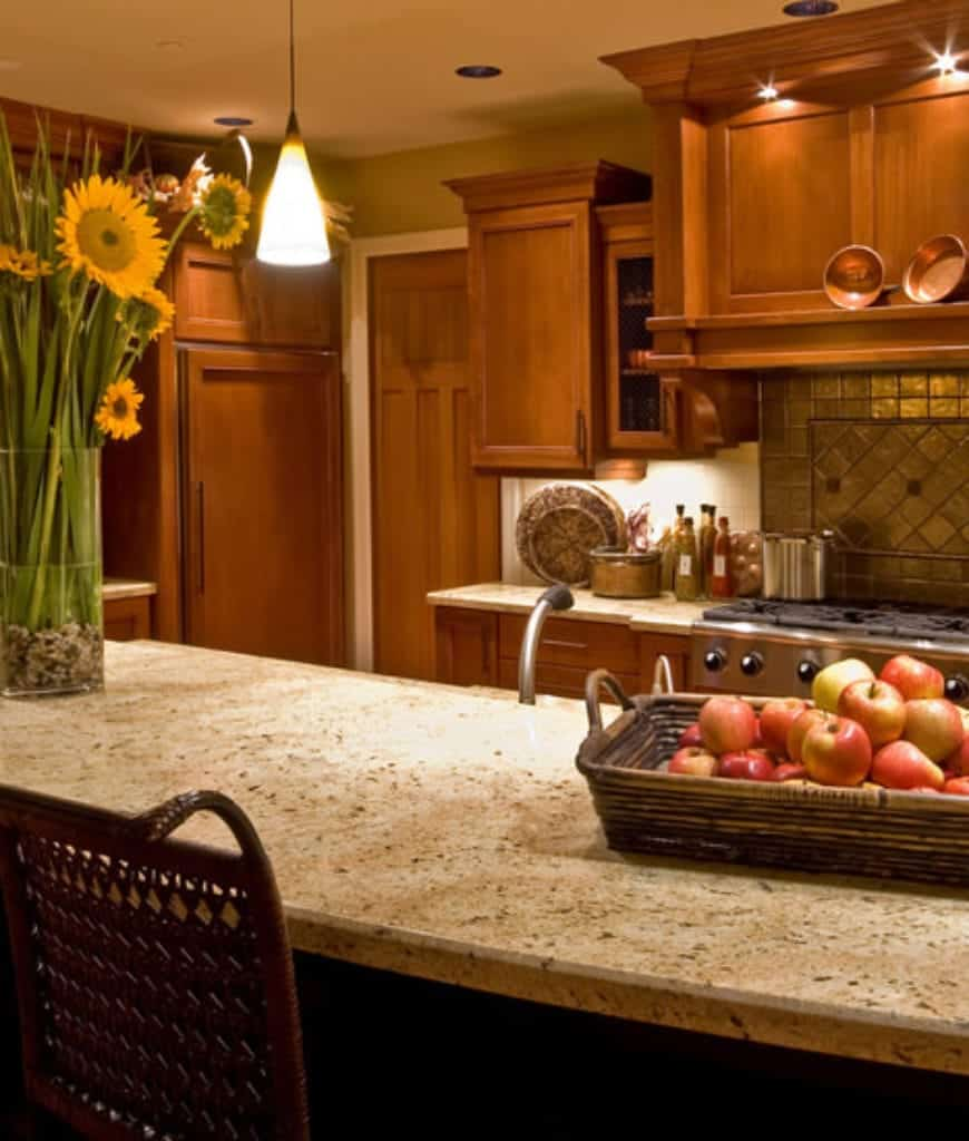 Warm kitchen filled with wooden cabinetry and a two-tier breakfast bar topped with granite counters and lighted by a glass pendant.